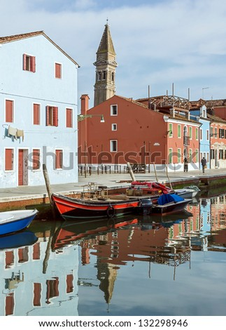 The colored houses on the shore of the channel near the old Church and leaning Tower - Burano, Venice, Italy