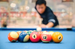The colorful billiard or pool balls for snooker game are on blue billiard table for starting the match with blur image of player.