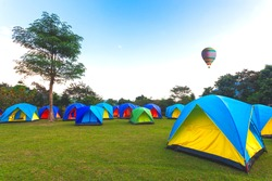 The Colorful Camping Tents with hot air balloon fly on the sky  on a glade and sunrise  in the national park near the mountain in the morning light on blue sky cloud