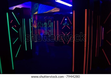 The colorful florescent lights of a laser game room with a blurred laser player.