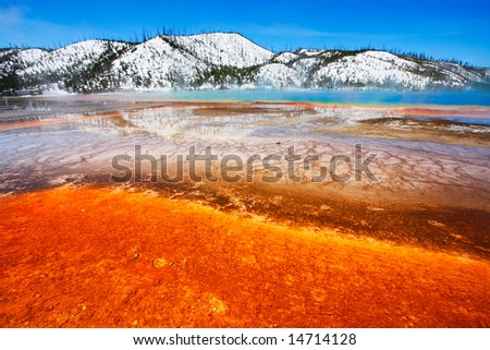 The colorful Grand Prismatic Spring with snow-covered hills - Midway Geyser Basin of Yellowstone National Park.