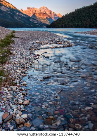 The colorful rocks in this river lead the eye to the beautiful orange lit mountain in the background.