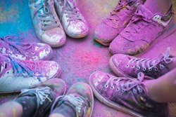 The colorful shoes and legs of teenagers at color run event