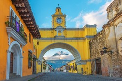 The colorful yellow arch of Antigua city at sunrise with the active Agua volcano in the background, Guatemala.