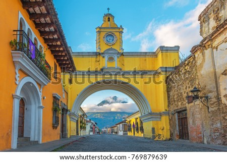 Shutterstock The colorful yellow arch of Antigua city at sunrise with the active Agua volcano in the background, Guatemala.