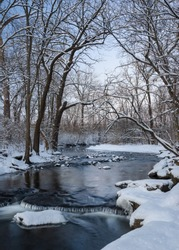 The colors of dusk settle over a secluded stream at the close of a winter day.