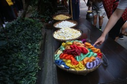 The colourful silk threads made from silkworm and cocoons place on bamboo basket for tourist visiting