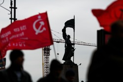 The communist flag is developing against the background of the White Guard monument in Vladivostok