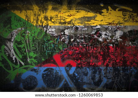 the Comoros flag painted on dirty street wall with graffiti texture background. National political symbol street art. #1260069853
