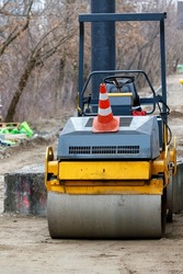 The compact road roller stands on a construction site with a leveled sand base for subsequent paving slabs. Vertical image. Copy space.