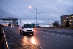 The compact van for the transport of commercial goods and parcels, as well as for use in a small business, traveling on the evening road in the twilight reflecting light on the wet rain highway