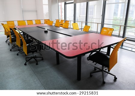 The company meeting room with big wood table and chairs.
