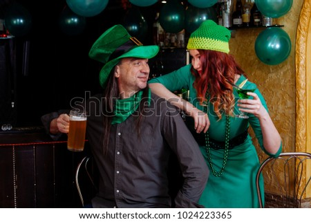 The company of young girls and one man celebrate St. Patrick's Day. They have fun at the bar. They are dressed in carnival headgear, green hats and clothes.