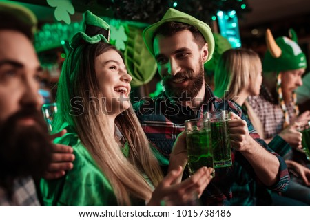 The company of young people celebrate St. Patrick's Day. They have fun at the bar. They are dressed in carnival headgear.