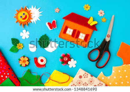 The composition of crafts made of felt. View from above. Sheets of felt, crafts made of felt, scissors, thread and needle for needlework. Hobbies and colorful crafts.