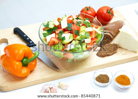 The composition of salad with fresh vegetables on the kitchen table - stock photo