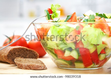 The composition of salad with fresh vegetables on the kitchen table