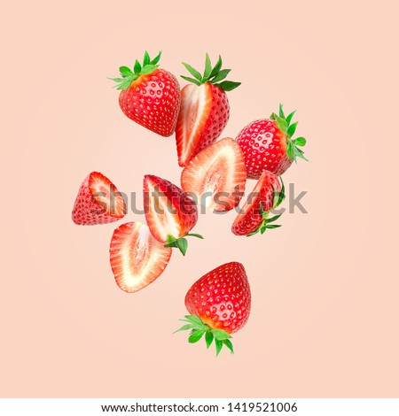 The composition of strawberries on a colored background. Cut strawberries into pieces with copy space. Fresh natural strawberry isolated. Strawberry slices flying in the air