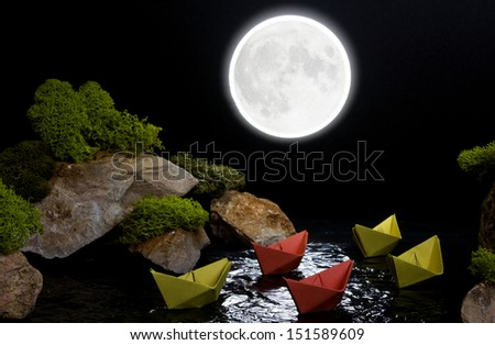 The composition of the stones, moss and paper boats, depicting sailing across the night sea between cliffs. The concept of a fragile dream world.