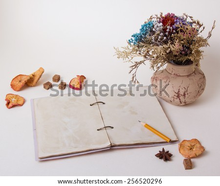 The composition of the vase on the table with dried flowers, apples and old notebook. Retro, vintage