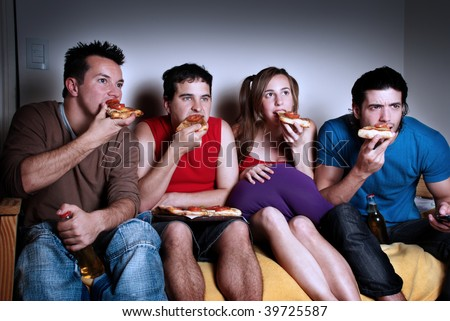 The concentrated fans with a pizza in hands, watching TV