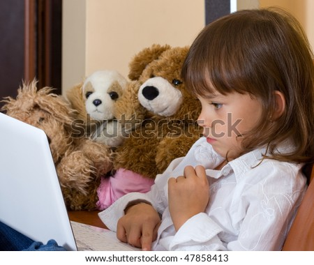 The concentrated girl works behind a portable computer. Soft toys observe of its work.