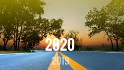 The Concept for new year 2020.The word 2019 growing to 2020 written on highway road in the middle of empty asphalt road at golden sunset and beautiful blue sky.