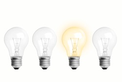 The concept is creative ideas. Image of 4 light bulbs arranged in 1 tube with yellow light. All are on a white background.