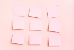 The concept is pink. Blank square small sheets of paper to write in even rows on a pink background. Top view