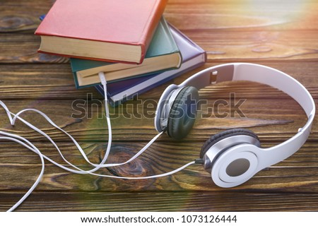 The concept is to listen to audiobooks. white headphones are connected to the book. Stockfoto ©