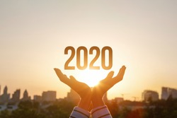 The concept new 2020 year. Hands show 2020 on the background of sunset.