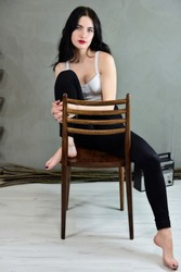 The concept of a glamorous female portrait. Portrait of a pretty brunette girl with long hair with excellent makeup in jeans and a T-shirt on a gray background sitting on a chair.