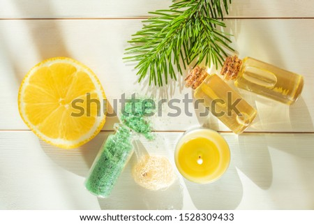 The concept of aromatherapy, relaxation, organics. Transparent bottles with aromatic oil and sea salt, spruce branch, lemon, candles on a light wooden background. Organic Apothecary #1528309433