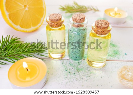 The concept of aromatherapy, relaxation, organics. Transparent bottles with aromatic oil and sea salt, spruce branch, lemon, candles on a light wooden background. Organic Apothecary #1528309457