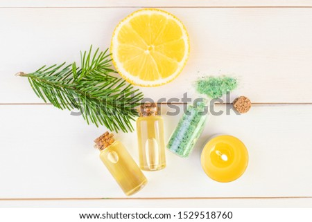 The concept of aromatherapy, relaxation, organics. Transparent bottles with aromatic oil and sea salt, spruce branch, lemon, candles on a light wooden background. Organic Apothecary #1529518760