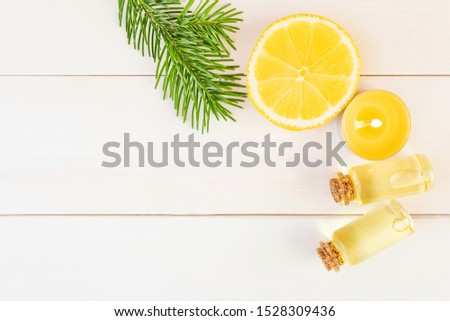 The concept of aromatherapy, relaxation, organics. Transparent bottles with aromatic oil, spruce branch, lemon, candle on a light wooden background. Organic apothecary. Place for text. #1528309436