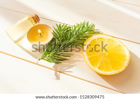 The concept of aromatherapy, relaxation, organics. Transparent bottles with aromatic oil, spruce branch, lemon, candle on a light wooden background. Organic apothecary. Place for text.