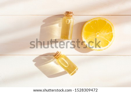 The concept of aromatherapy, relaxation, organics. Transparent bottles with essential oil, lemon on a light wooden background. Organic apothecary. Place for text. Minimalism, top view, flat lay.