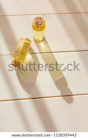 The concept of aromatherapy, relaxation, organics. Transparent bottles with essential oil on a light wooden background. Organic apothecary. Place for text. Minimalism, bright sunlight. #1528309442