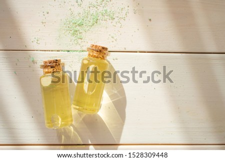 The concept of aromatherapy, relaxation, organics. Transparent bottles with essential oil on a light wooden background. Organic apothecary. Place for text. Minimalism, bright sunlight.