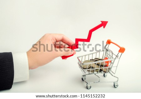 the concept of attracting investments, increasing the average check in the store. The businessman's hand holds the arrow up above the supermarket trolley. growth of the economy. capital building #1145152232