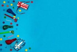 The concept of birthday. A border of gift boxes, balloons, confetti, cake candles and blowouts on a light blue background. Free space.