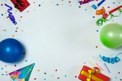 The concept of birthday. The frame is made of gift boxes, confetti and streamers, cone-shaped caps, blowouts, cake candles and balloons on a light gray background.