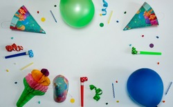The concept of birthday. The frame is made of paper decorations, confetti and serpentine, cone-shaped caps, blowouts, cake candles and balloons on a light gray background.