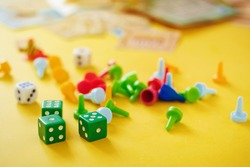 The concept of board games. Dice, chips and cards on a yellow background