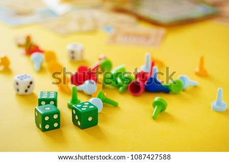 The concept of board games. Dice, chips and cards on a yellow background #1087427588