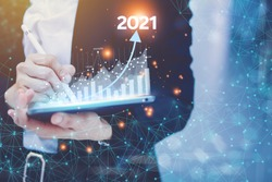 The concept of business people setting business goals Turn it into a 2021 concept by holding a virtual screen showing the 2021 year graph of trade growth and revenue.