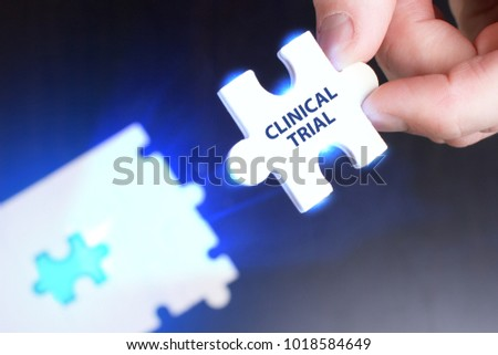 The concept of business, technology, the Internet and the network. A young businessman collects a puzzle with the proper inscription: Clinical trial #1018584649