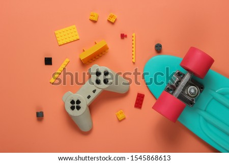 The concept of childhood, entertainment. Cruiser board, gamepad, toy bricks on coral color background. Summer fun. Studio shot. Top view stock photo