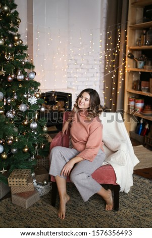 The concept of Christmas home shooting. Beautiful attractive cute brunette girl with short hair in warm home clothes sitting on a chair near the Christmas tree on the background of the fireplace. #1576356493